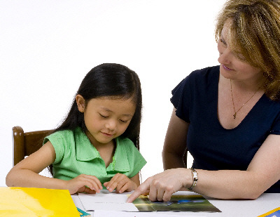 An adult helps a child with a written task.