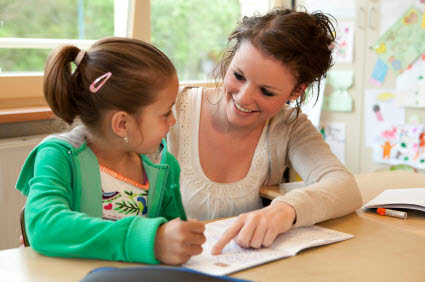 A smiling Educational Psychologist works with a smiling child.